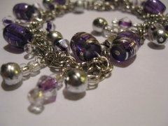 Dangle Bracelet with a simple 2 in 2 with bright aluminum and various purple beads.